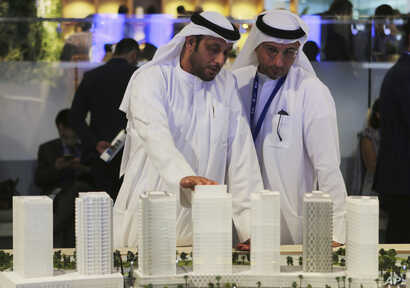 People look at an architectural model of a housing development at the Cityscape Global exhibition, in Dubai, United Arab Emirates,  Sept. 11, 2017.