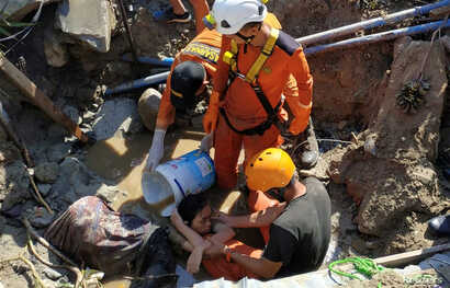 Search and rescue workers help rescue a person trapped in rubble following an earthquake and tsunami in Palu, Central Sulawesi, Indonesia, Sept. 30, 2018.