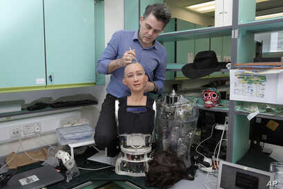 FILE - David Hanson, founder of Hanson Robotics, works on his company's flagship robot Sophia, in Hong Kong,  Sept. 28, 2017. Sophia is a creation of the Hong Kong-based startup working on bringing humanoid robots to the marketplace.