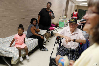 Korea War veteran, Ed Coddington, 83, second from right, and wife Esther, 78, wait with Markia McCleod, rear, her aunt Ernestine McCleod and daughter Keymoni, 4, in a shelter for Hurricane Florence to pass after evacuating from their nearby homes in ...