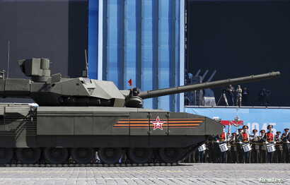 A Russian serviceman holds a red flag onboard a T-14 Armata tank after it stopped during a rehearsal for the Victory Day parade in Red Square in central Moscow, Russia, May 7, 2015.
