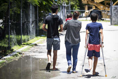 FILE - Refugees are pictured on Nauru, Sept. 4, 2018. Psychiatric and physical suffering of children has been the major criticism of the government's policy since 2013 to send asylum seekers who attempt to reach Australia by boat to an immigration ...