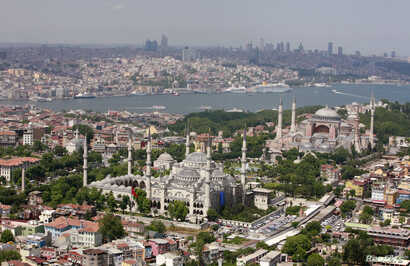 FILE - The Ottoman-era Blue Mosque and the sixth-century Byzantine monument of Hagia Sofia (Ayasofya) are seen in the old city as skyscrapers of the city's financial district stand in the background over the port of Istanbul June 1, 2007.