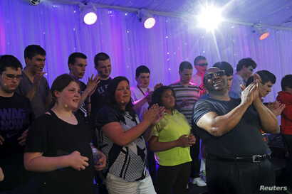 FILE - Ellis Hall, right, a rhythm-and-blues singer and an alumnus of the Perkins School for the Blind, rehearses with the Perkins Chorus, made up of visually impaired and blind students, for the school's annual gala in Watertown, Mass., May 7, 2015....