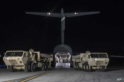 In this photo provided by U.S. Forces Korea, trucks carrying U.S. missile launchers and other equipment needed to set up the Terminal High Altitude Area Defense (THAAD) missile defense system arrive at the Osan air base in Pyeongtaek, South Korea, Ma...
