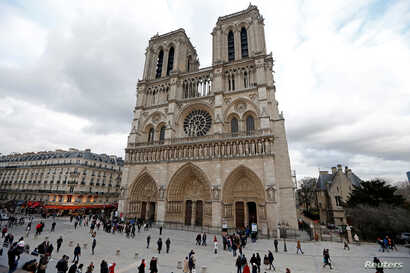 FILE - People walk past the entrance to the Notre Dame Cathedral in Paris, Feb. 8, 2013.
