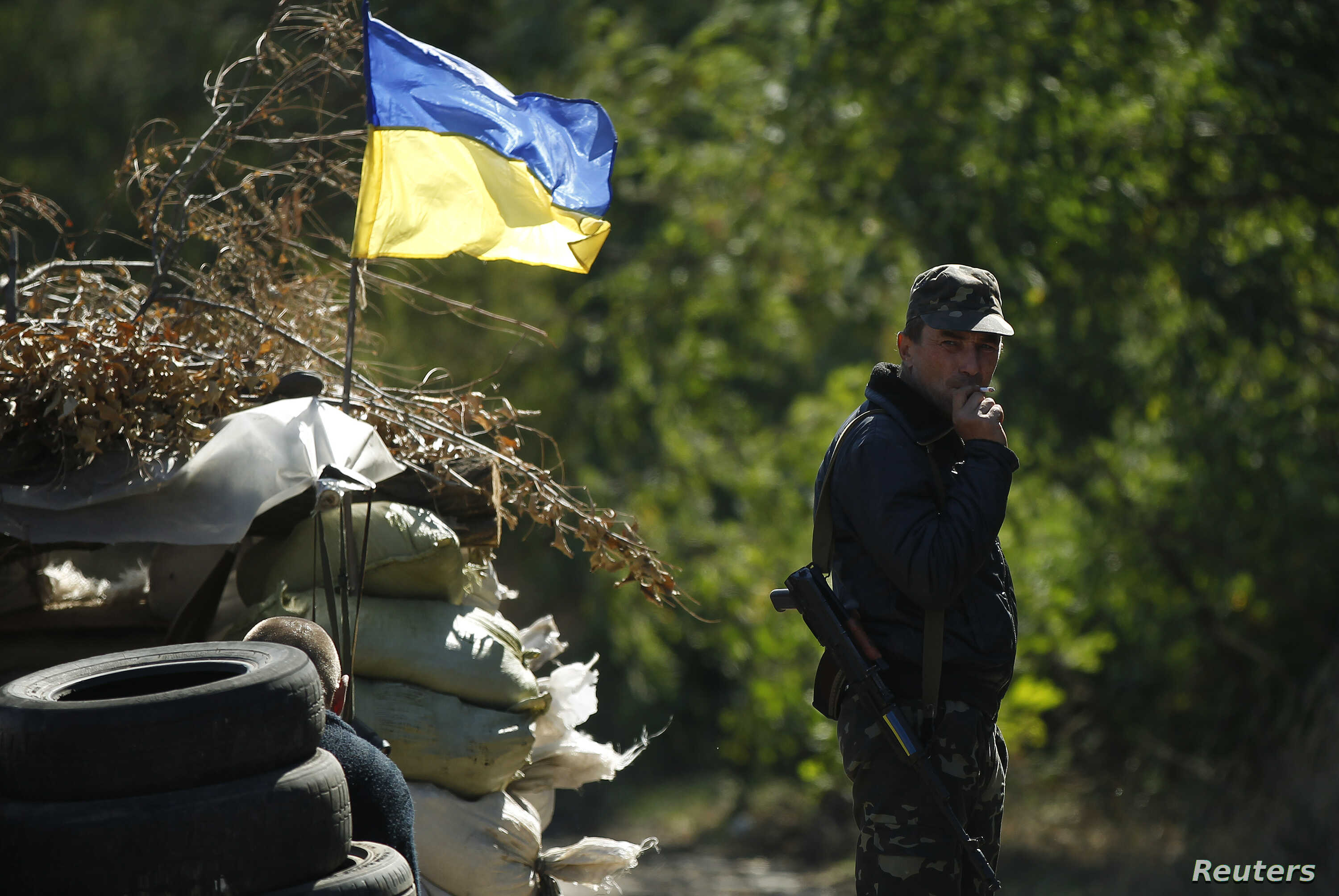 A Ukrainian serviceman smokes at a checkpoint near the town of Horlivka, Donetsk region, in eastern Ukraine, Sept. 18, 2014.
