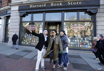 """Students pose for a selfie outside the Harvard Book Store, March 9, 2017, in Cambridge, Mass. Readers have been flocking to classic works of dystopian fiction. Some have shot to the top of best-seller lists, including George Orwell's """"1984"""" and Marga"""