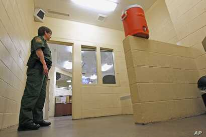FILE - A Border Patrol agent stands inside one of the holding areas at the Tucson Sector of the U.S. Customs and Border Protection headquarters in Tucson, Ariz., Aug. 9, 2012.