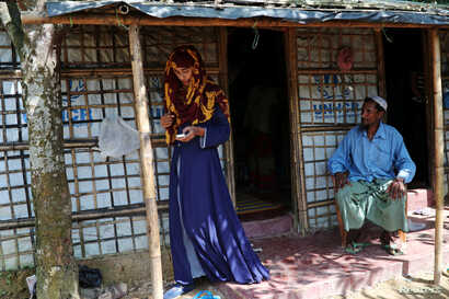 Formin Akter uses her mobile phone as her father Mohammad Hossain watches before she departs for Chittagong to attend school at the Asian University for Women, Aug. 24, 2018.