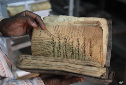A man holds an ancient manuscript from Timbuktu that will need to be restored after being damaged by Islamic extremists in Bamako, Mali, Jan. 27, 2015.