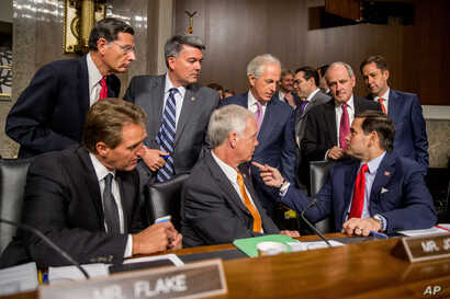 Members of the Senate committee speak together before Secretary of State John Kerry, Secretary of Energy Ernest Moniz and Secretary of Treasury Jack Lew arrive to testify at a Senate Foreign Relations Committee hearing on Capitol Hill, in Washington,...