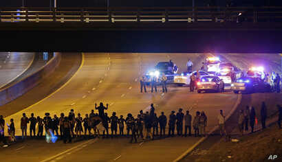 Police confront protesters blocking I-277 during demonstrations following Tuesday's police shooting of Keith Lamont Scott in Charlotte, N.C., Thursday, Sept. 22, 2016.