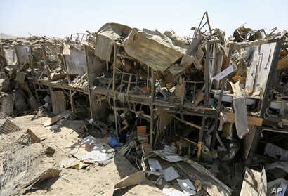 A security guard stands amid the damage of a truck bombing, in Kabul, Afghanistan, Monday, Aug. 1, 2016.
