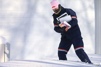 U.S. Postal Service letter carrier Jamie Jasmon struggles through snow and below zero temperatures while delivering the mail, Jan. 6, 2014,  Springfield, Illinois.