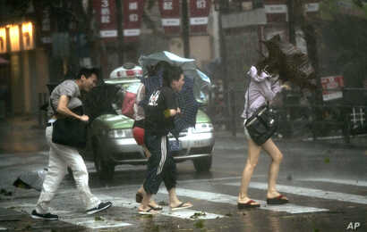 People walk in a rainstorm brought on by Typhoon Haikui in Shanghai, China, August 8, 2012.
