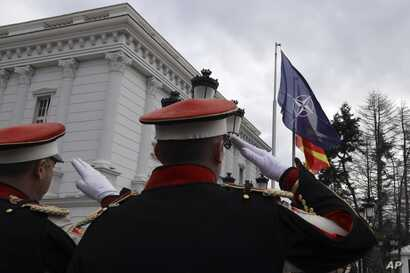 Macedonian soldiers salute as the NATO flag raising in front of the government building during a ceremony in Skopje, Feb. 12, 2019.