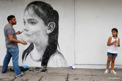 Ariadna Herrera, 6, poses for Cuban artist Maisel Lopez as he paints the wall of a state art gallery in Havana, April 18, 2017.