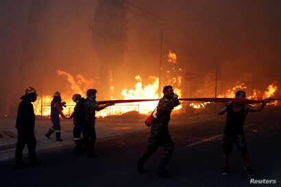 Firefighters, soldiers and local residents carry a hose as a wildfire burns in the town of Rafina, near Athens, Greece, July 23, 2018.
