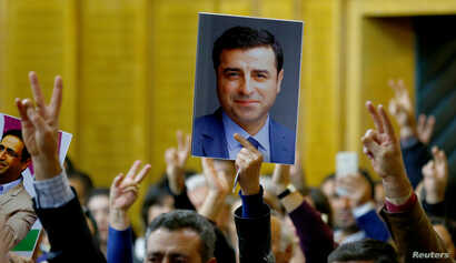 A supporter holds a portrait of Selahattin Demirtas, detained leader of Turkey's pro-Kurdish opposition Peoples' Democratic Party at a meeting at the Turkish parliament in Ankara, Nov. 8, 2016.