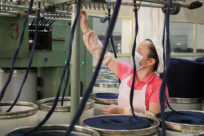 FILE - A worker checks a machine that arranges thick yarn at a factory owned by Hong Kong's Novetex Textiles Limited in Zhuhai City, Guangdong province, China, Dec. 13, 2016. A new Novetex spinning mill, the first to open in Hong Kong in half a centu...