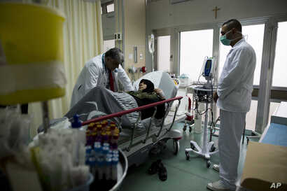A doctor treats a woman with respiratory difficulties at the emergency room at Sacre Couer hospital outside Beirut, Lebanon, March 3, 2016.