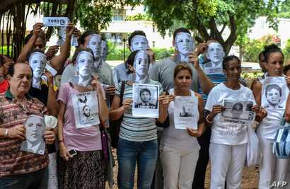 Cuban dissidents pose wearing masks depicting US President Barack Obama and holding pictures of imprisoned dissidents as they protest against the reopening of the US embassy in the island, Aug. 9, 2015.