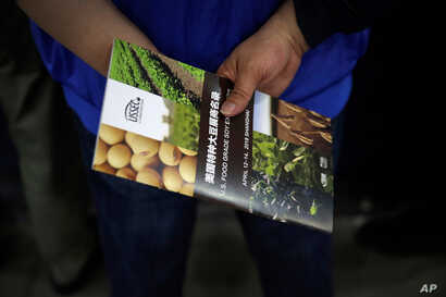 FILE - A Chinese visitor holds a U.S. soybean company's leaflet at the international soybean exhibition in Shanghai, April 12, 2018.