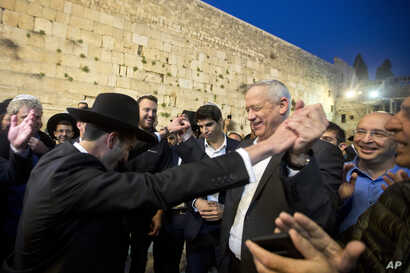 Leader of the Blue and White party, former Israeli army chief of staff, Benny Gantz, right, dances with ultra Orthodox Jewish men at the Western Wall, in Jerusalem's Old City, March 28, 2019.