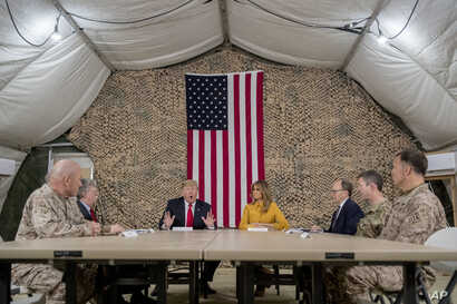 President Donald Trump, accompanied by National Security Adviser John Bolton, third from left, first lady Melania Trump, fourth from right, US Ambassador to Iraq Doug Silliman, third from right, and senior military leadership, speaks to members of th...