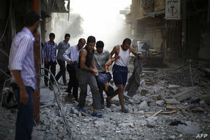 Syrians carry a wounded man following reported air strikes by Syrian government forces on the rebel-held town of Douma, east of the Syrian capital Damascus, on Oct. 2, 2015.