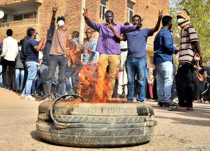 Sudanese demonstrators burn a tire as they participate in anti-government protests in Khartoum, Sudan, Jan. 17, 2019.