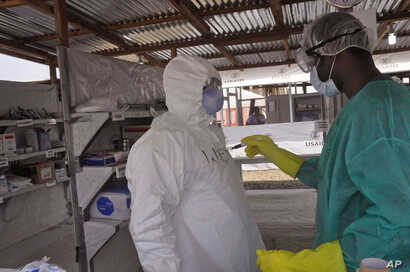 FILE - A health care worker assists a colleague inside a USAID,  funded Ebola clinic in Monrovia, Liberia, Jan. 30, 2015.