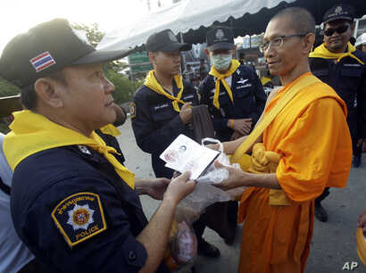A Thai policeman checks identity card of a Buddhist monk of the Dhammakaya sect temple for security outside the temple in Pathum Thani, north of Bangkok, Thailand, Feb. 22, 2017.