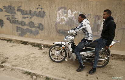 """Unemployed men sit on motorcycle beside a graffiti which reads """"Marginalized youth"""" at the impoverished Zhor neighborhood of Kasserine, where young people have been demonstrating for jobs since last week, January 28, 2016. REUTERS/Zohra Bensemra"""