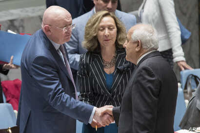 Russia's Ambassador to the United Nations  Vassily Nebenzia, left, greets Palestinian Ambassador  Riyad Mansour before a Security Council meeting on the situation between the Israelis and the Palestinians, Friday, June 1, 2018.