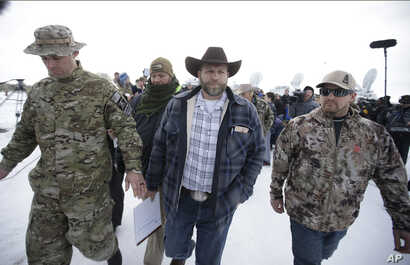 Ammon Bundy, center, one of the sons of Nevada rancher Cliven Bundy, walks off after speaking with reporters during a news conference at Malheur National Wildlife Refuge headquarters Jan. 4, 2016, near Burns, Ore.