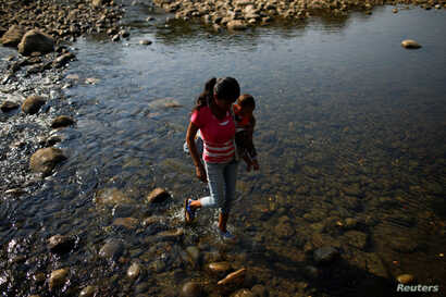 A woman carrying a child walks across the Tachira river on the outskirts of Cucuta, on the Colombian-Venezuelan border, Colombia, Feb. 25, 2019.