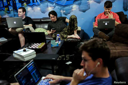 """Zander Dejah (2nd L), 25, who works as a Virtual Reality engineer, Nick Olszowy (C), 25, a software engineer and Andrew Bresee, 26, a software engineer, all who are residents of The Negev tech house, use their electronics during a Sunday """"family"""" din..."""