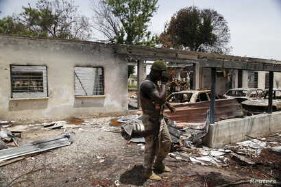 A soldier walks through the burnt building at the headquarters of Michika local government in Michika town, after the Nigerian military recaptured it from Boko Haram, in Adamawa state, May 10, 2015.