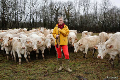 Emilie Jeannin, 37, a cow breeder, poses for a photograph with her Charolais cows in Beurizot, France, Feb. 21, 2017.