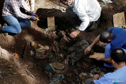 Members of the forensic team and auxiliary workers work at an exhumation site in the village of La Joya as they search for human remains of the EL Mozote massacre in the town of Meanguera, El Salvador, Nov. 24, 2016.