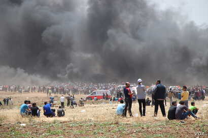 Tear gas hits people on the ground who are partially masked by smoke from tires that Palestinian protesters burn to create cover in Gaza, May 14, 2018.