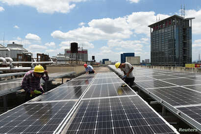 Employees install solar panels at a roof of Yiwu International Trade City in Yiwu, Zhejiang province, China, July 17, 2017.