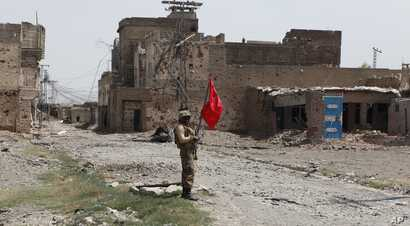 A Pakistani army soldier stands guard in Miranshah bazaar after driving out militants from Pakistan's tribal region of North Waziristan along the Afghanistan border,  July 9, 2014.