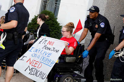 Capitol Police detain a demonstrator as the Senate Finance Committee holds a hearing on the latest Republican effort to repeal and replace the Affordable Care Act in Washington, Sept. 25, 2017.