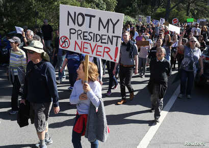 FILE - A woman holds a sign during a protest against President-elect Donald Trump at Golden Gate Park in San Francisco, California, Nov. 13, 2016.