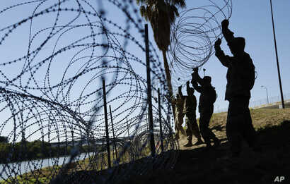 FILE - Members of the U.S. military install multiple tiers of concertina wire along the banks of the Rio Grande near the Juarez-Lincoln Bridge at the U.S.-Mexico border, Nov. 16, 2018, in Laredo, Texas.