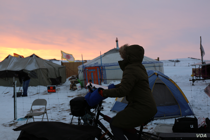 A volunteer pedals a stationary bike set up to power a strip of phone chargers in the media tent of the Standing Rock camp in North Dakota. (E. Sarai/VOA news)