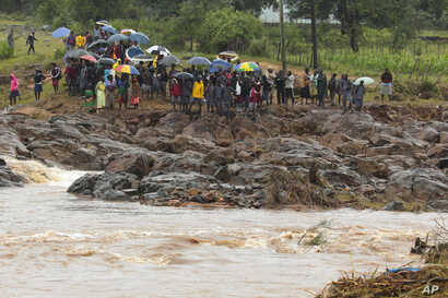 Schoolchildren are stranded across a collapsed bridge in Chimanimani, southeast of Harare, Zimbabwe, March 18, 2019.